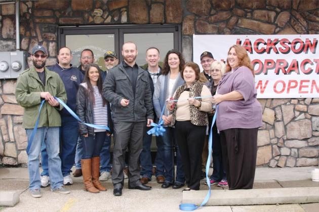 Dr. Ryan Jackson (front, center) is joined by local officials and family and friends at last week's ribbon-cutting ceremony.