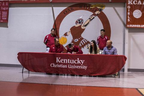 Coach Joey Kirby and Assistant Coach Adam Kirby look on as Cory Mason signs.  Joining Cory at the table are KCU Coach Grady Lowe and his parents Lori and Glen Mason.