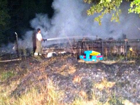 Fifth District fireman Richard Henderson helps put out the fire on Oak Ridge Road.