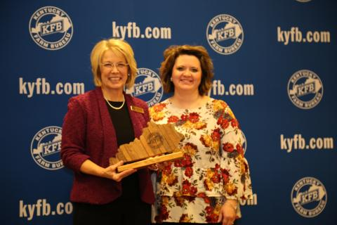 Sherri Kirby of the Butler County Farm Bureau Women's Committee, accept the 2018 Gold Star Award of Excellence from Vicki Bryant, chair of the Kentucky Farm Bureau state Women's Committee. The award was presented during a November 30 recognition program at the 99th Kentucky Farm Bureau annual meeting.