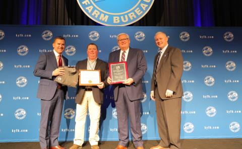 Shane Wells, President of Butler County Farm Bureau (center left), accepts the award from John Sparrow, Executive Vice President and CEO of KFB Insurance (left), Mark Haney, President of Kentucky Farm Bureau (center right), and Drew Graham, Executive Vice President of the KFB Federation (right), during a Dec. 6 recognition and awards program.