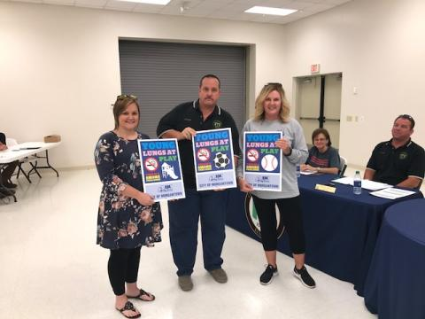 """Butler County Drug-Free Coalition employees Rhonda Vaughn and Ali Johnson presented Mayor Phelps with new signs for the park that say, """"Young lungs at play. This is a smoke free zone."""""""