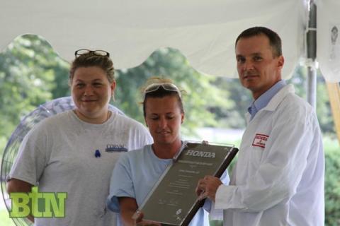 Corvac employees Dana Gill and Tiffany Flener accepts the award from Mark VanDeVelde of Honda.