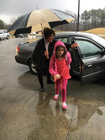 MES Counselor JoLynn Reed helps Cheyenne Givens, a kindergarten students in Mrs. Stokes class try to stay dry on a rainy day.