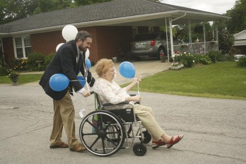 Morgantown Care and Rehabilitation Center Chaplain Derek Cain and an elder prepare to release balloons Thursday.
