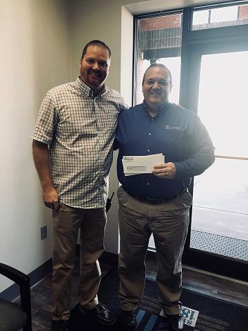 Jason Jones presents quarterly Spirit Card checks to Cody Donaldson, BCMS Assistant Principal.