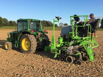 Technicians plant 4 row plots for the Kentucky Corn Variety Trial.  The technician riding the planter is changing corn hybrids on the go by dumping a small amount of seeds as the planter moves down the field.  The tractor is operating on auto-steer to insure even spacing between planter passes.