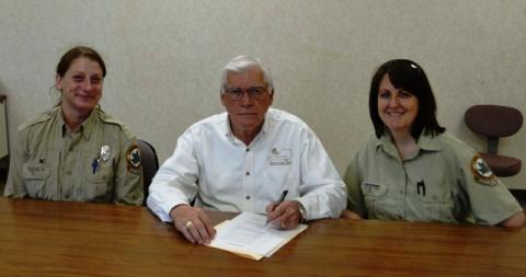 Forest ranger Susan Nightingale (left) and forester Chris Oelschlager (right) are present as Judge Executive David Fields signs an Arbor Day Proclamation.