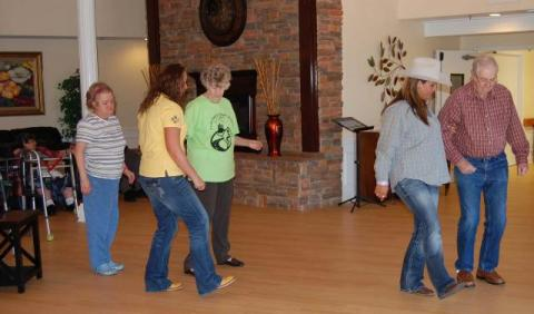 Leah Burden and Ashley Flint (foreground) teach a new dance step to Linda Gray,