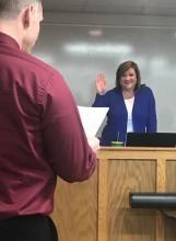 Assistant Superintendent Robert Tuck administers the Oath of Office to newly-reelected Board member Amy Hood