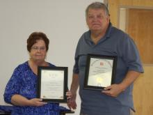 "Sue Embry and Fred Tate display the ""Yes We Did Award"" and the ""Gold Star Award."""